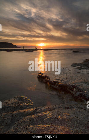 Two young men fishing on the shore at Staithes on the North Yorkshire coast at sunset in mid-summer. - Stock Photo