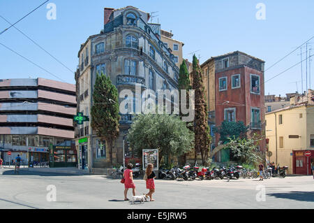 People crossing road, building behind has 3D effect mural on end wall, Montpellier, France. - Stock Photo
