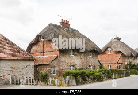Traditional brick built thatched cottages in East Stratton, a small country village near Winchester, Hampshire, - Stock Photo