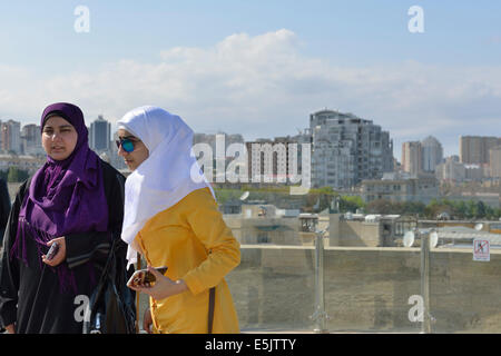Two women on viewing platform of the Maiden Tower, Old City, Baku, Azerbaijan - Stock Photo