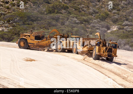 Scrapper working moving sand on new Australian coastal suburb. Working in tandem. Moving sand. - Stock Photo