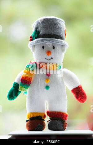 Knitted snowman with bright cheery colors, green Bokeh - Stock Photo
