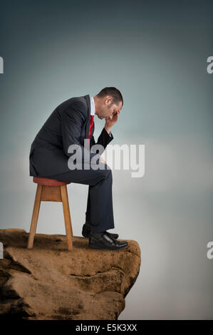 depressed businessman suffering depression on a cliff ledge - Stock Photo