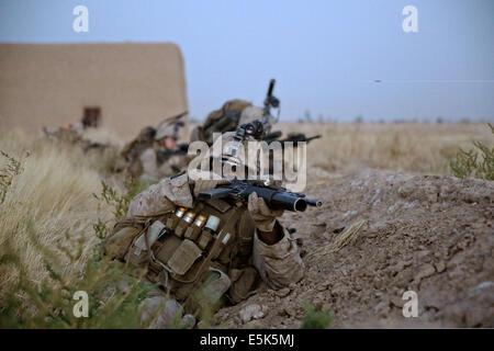 US Marine Cpl Deshaun Jackson, rifleman, Bravo Company, 1st Battalion, 7th Marine Regiment, takes cover behind a - Stock Photo