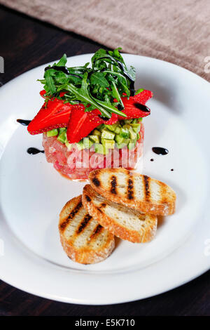 Tuna tartare with fruit strawberries and toasted toast shot close-up in a restaurant - Stock Photo