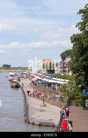 DEVENTER, THE NETHERLANDS - AUGUST 3, 2014. A long stripe of book stalls crowded with people along the riverside. - Stock Photo