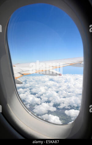 Passengers view of aeroplane window frame and aircraft wing with white clouds and a blue sky Flying over Europe - Stock Photo