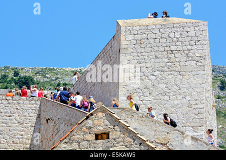 Young tourists walking up steps on the Dubrovnik city walls on a hot summers day (possibly a school group) - Stock Photo