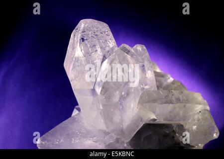 Quartz crystal illuminated with purple glowing background. - Stock Photo