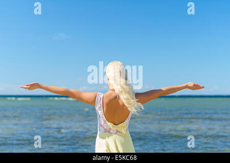 Young woman with arms wide open. Place for text. - Stock Photo