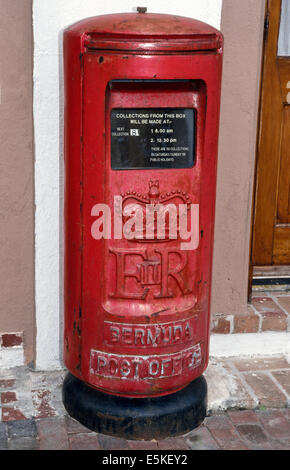 A vintage red pillar postal box awaits mail on a street in Hamilton, capital of Bermuda, a British Overseas Territory - Stock Photo