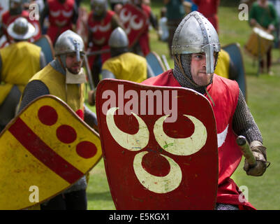 Beeston, Cheshire, UK 3rd August, 2014.  Helmeted armed fighting re-enactors with red & yellow shields, at the Medieval - Stock Photo