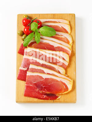Sliced prosciutto crudo on cutting board - Stock Photo