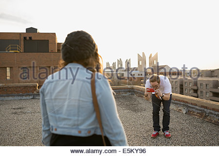 Man photographing woman on urban rooftop - Stock Photo
