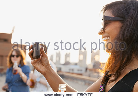 Smiling woman taking photos at urban rooftop party - Stock Photo