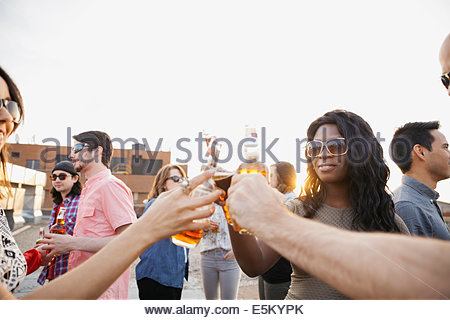 Friends toasting beer bottles at rooftop party - Stock Photo