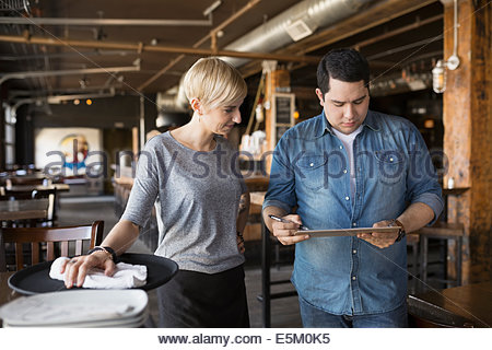 Pub owner and server looking at clipboard - Stock Photo