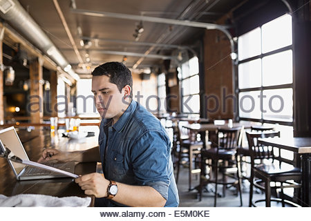 Pub owner reviewing clipboard - Stock Photo