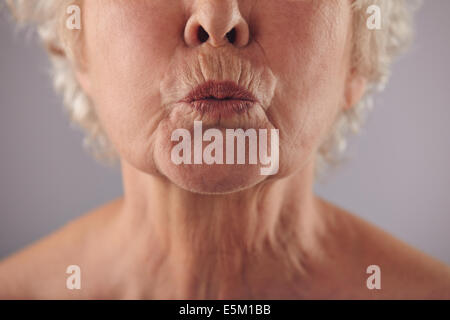 Close-up portrait of mature woman puckering lips against grey background. Senior woman grimacing. Focus on lips. - Stock Photo