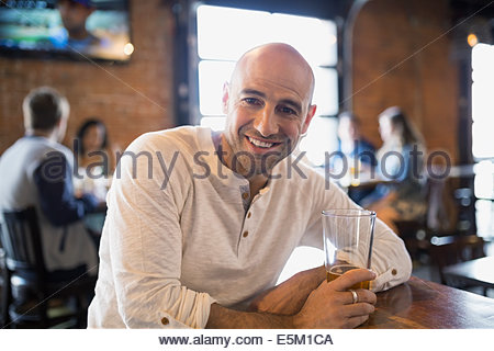 Portrait of smiling man drinking beer in pub - Stock Photo