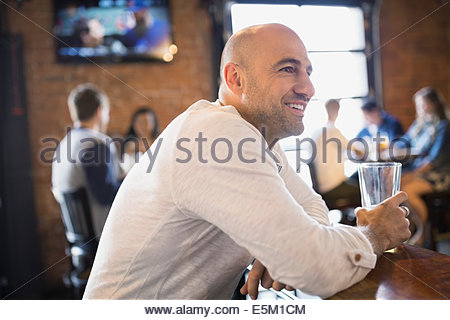 Smiling man drinking beer in pub - Stock Photo