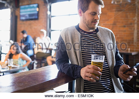 Man with beer text messaging in pub - Stock Photo