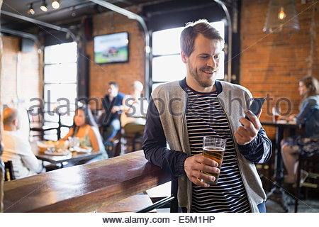 Smiling man with beer text messaging in pub - Stock Photo