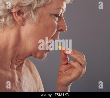 Side view of mature woman taking a tablet against grey background. Time for medication. Old woman having a medicine - Stock Photo