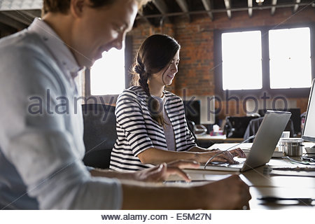 Businesswoman working on laptop in office - Stock Photo