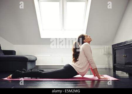 Side view of a fit young woman doing yoga exercise on mat at home. Female stretching her back while lying on floor. - Stock Photo