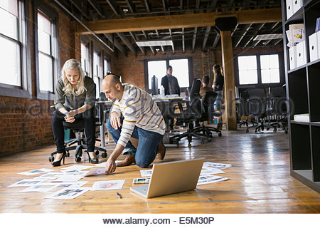 Business people reviewing proofs on floor in office - Stock Photo