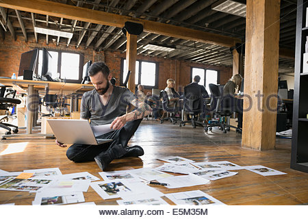 Businessman reviewing proofs on floor in office - Stock Photo