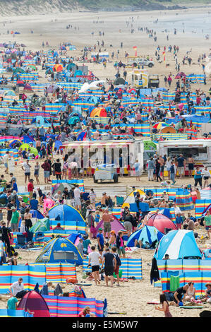 Windbreaks line the beach as thousands of sunbathers enjoy the summer hot weather on a busy day at Woolacombe beach, - Stock Photo
