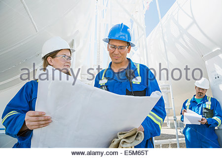 Workers reviewing blueprints at gas plant - Stock Photo