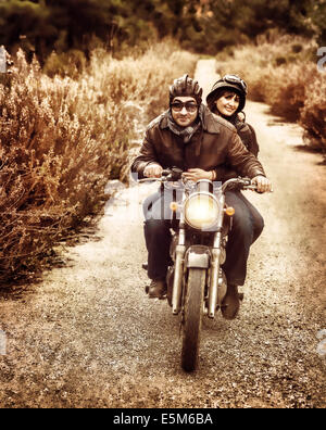 Vintage style image of two happy bikers riding on the road, active family enjoying journey on luxury extreme transport - Stock Photo