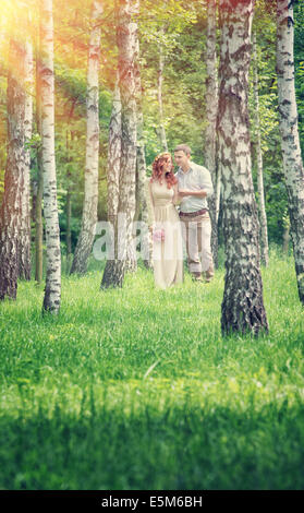 Loving couple walking between birch in the park in sunny day,  holding hands, happy wedding day, love and romance - Stock Photo