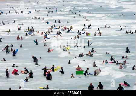 Sunbathers cool off in the sea on the busiest day of the year at Woolacombe beach, Devon, UK - Stock Photo