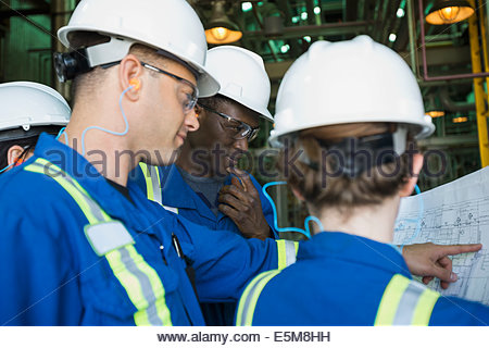 Workers reviewing blueprint in gas plant - Stock Photo