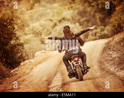 Sporty family traveling on motorbike, riding on motorcycle with raised up hands, active people, extreme sport, freedom - Stock Photo