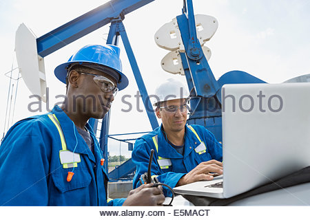 Male workers using laptop below oil well - Stock Photo