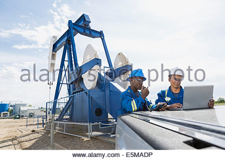 Male workers using laptop near oil well - Stock Photo