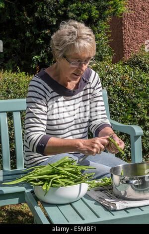 Older woman with rheumatoid arthritis in garden UK slicing home-grown green/runner beans ready for freezing for - Stock Photo