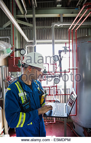 Male worker with laptop in gas plant - Stock Photo