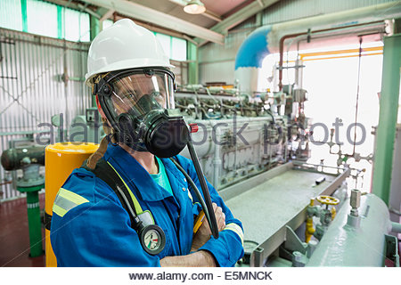 Male worker wearing respirator in gas plant - Stock Photo