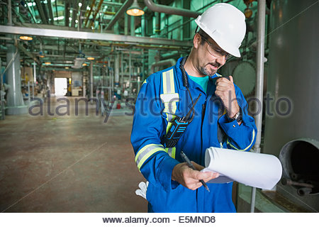 Male worker using walkie-talkie at gas plant - Stock Photo
