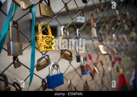 Couples place padlocks on the fence outside Shoreditch station, Brick Lane. East London, UK 2014 - Stock Photo