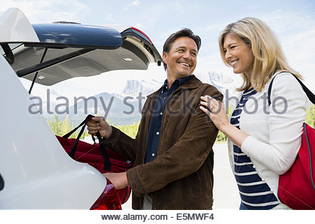 Couple loading luggage in hatchback of car - Stock Photo
