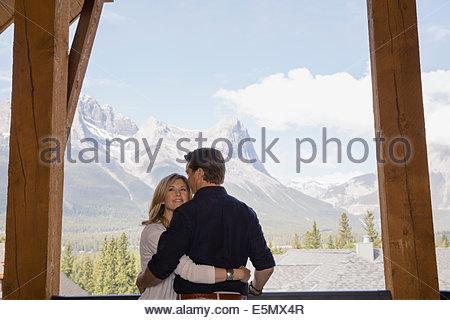 Couple hugging on balcony overlooking mountains - Stock Photo