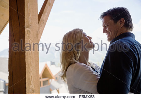 Couple hugging on balcony - Stock Photo