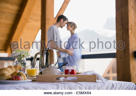 Breakfast on bed with couple in background - Stock Photo